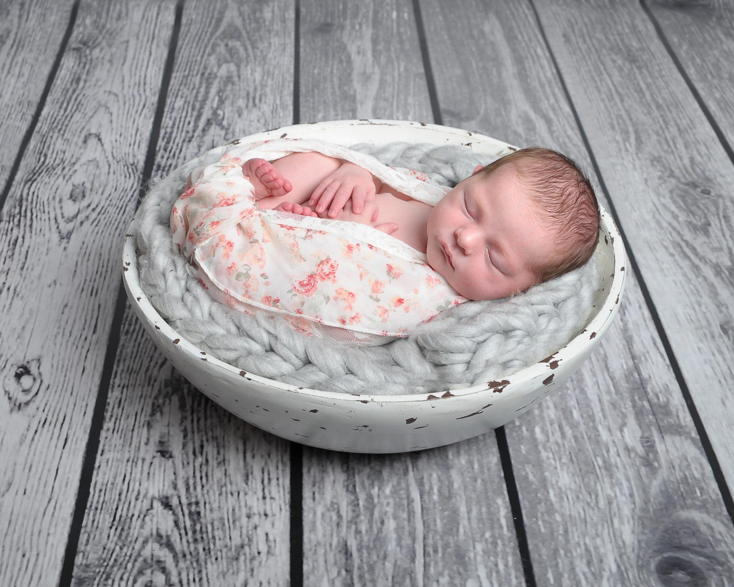 newborn baby girl sleeping in bowl