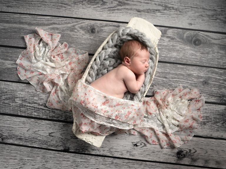 Newborn baby sleeping in trench bowl captured by Treasured Moments Photography