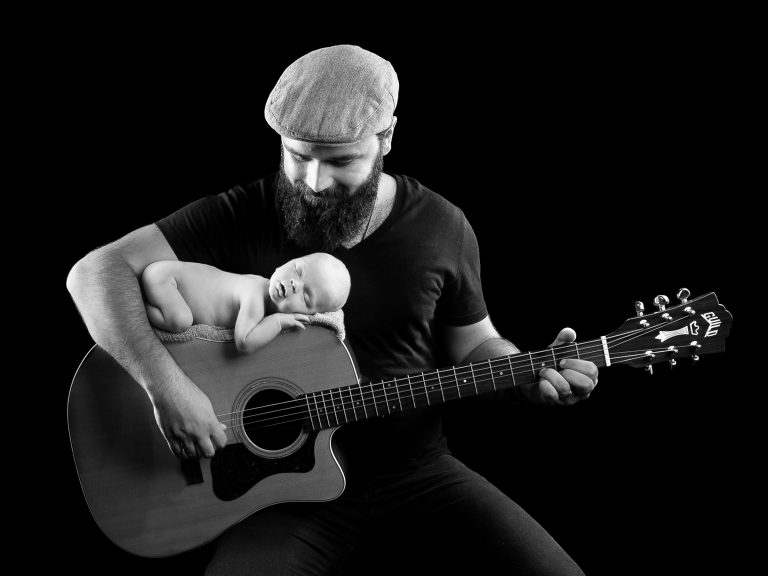 Newborn baby sleeping on dads guitar whilst day playing captured by Treasured Moments Photography