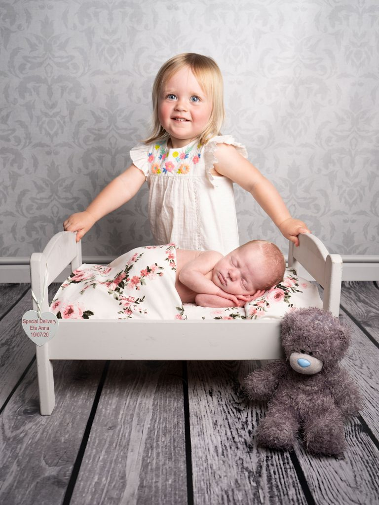 Sister looking after newborn baby sister captured by Treasured Moments Photography