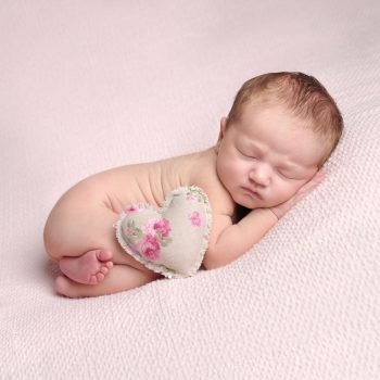 newborn baby laying on belly